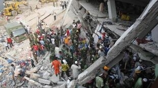 Firefighters, army and locals try to rescue garment workers, who are trapped inside the rubble of the collapsed Rana Plaza building, in Savar
