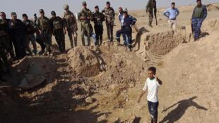 Les forces irakiennes sur le lieu où une fosse commune a été découverte au nord de la ville d'Hawija, libérée de l'EI en octobre dernier. (Photo prise le 11 novembre 2017).