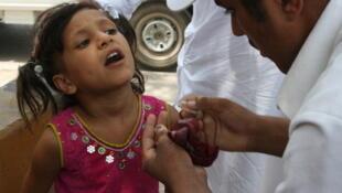 Peshawar, Pakistan, le 18 juillet 2011. Une petite fille reçoit quelques gouttes d'un vaccin contre la polio, dans une gare routière.