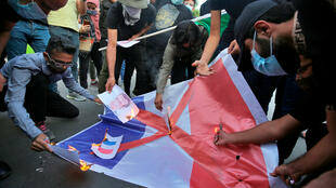 Des manifestants brûlant un drapeau français lors d'une manifestation à Bagdad, le 26 octobre 2020.