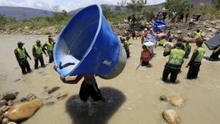 Colombianos cargados de sus pertenencias cruzan el río Táchira hacia su país, este 25 de agosto de 2015.