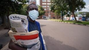 A newspaper seller carries a bundle of Rwanda's leading newspapers wearing a mask and gloves. Kigali has recorded 225 confirmed coronavirus cases, 26 March 2020