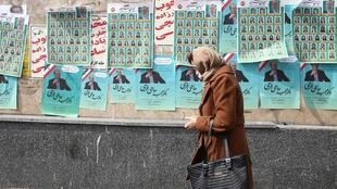 Uma mulher passa por cartazes de propaganda eleitoral em Teerã, em 19 de fevereiro de 2020.