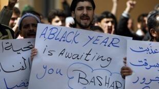 Opositores ao regime ostentam cartazes contra o presidente sírio Bachar al-Assad.