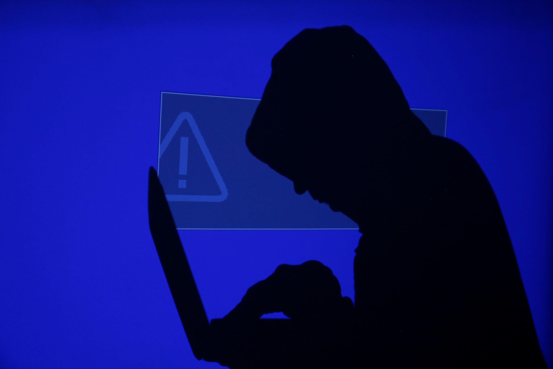 Un hombre encapuchado escribe en una computadora en esta ilustración realizada el 13 de mayo de 2017.