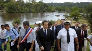 Après une courtes navigation en pirogue, le président Nicolas Sarkozy, entouré des autorités locales, arrive à Talwen, sur le fleuve Maroni.