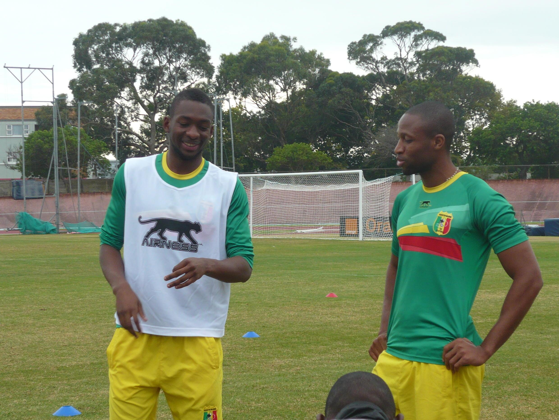 Les Maliens Samba Sow (à g.) et Seydou Keita (d.) plaisantent à l'entraînement.