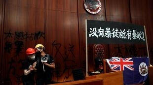 Anti-extradition bill protesters stand next to a colonial flag of Hong Kong and a banner displayed inside a chamber, after protesters broke into the Legislative Council building during the anniversary of Hong Kong's handover to China in Hong Kong, July 1.