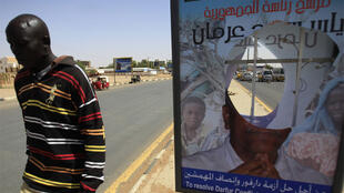 A man walks past a defaced SPLM election poster in Khartoum