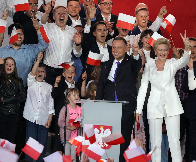 El presidente de Polonia, Andrzej Duda, y su esposa, Agata, hacen el símbolo de la victoria ante sus partidarios al conocer los sondeos a pie de urna de las elecciones el 12 de julio de 2020 en Pultusk