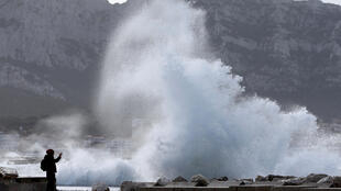 A man takes a picture as high waves hit the waterfront in Marseille after storm Eleanor hit France.