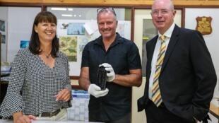 Le couple de découvreurs entre un expert du musée de Perth qui tient la fameuse bouteille entre ses mains.