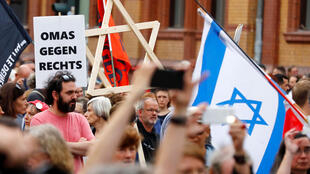 """Un homme portant une étoile de David en bois assiste à une manifestation portant le slogan """"#unteilbar"""" (indivisible) pour protester contre l'antisémitisme, le racisme et le nationalisme à Berlin, en Allemagne, le 13 octobre 2019."""