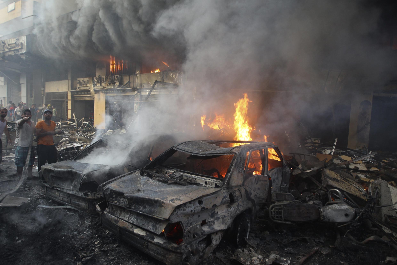 Partidários do Hezbollah tentam apagar o incêndio provocado pelo atentado desta quinta-feira