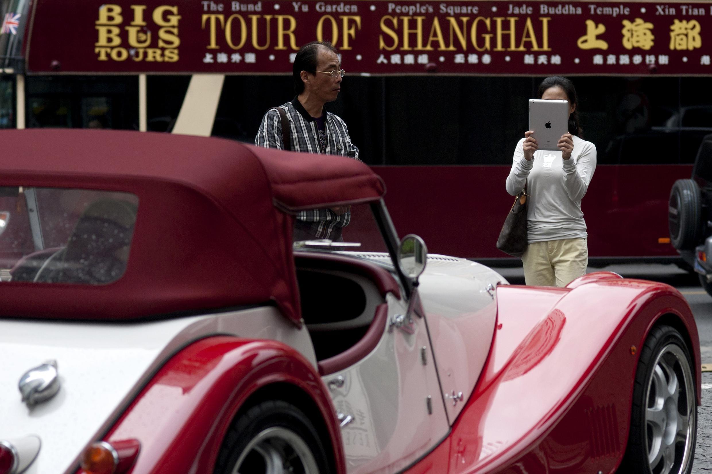 Une femme prend en photo, avec son iPad, une voiture de sport Morgan à Shangai, le 25 octobre 2012.