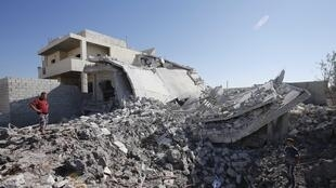 Civilians stand near a destroyed house after a Syrian Air Force fighter jet launched a bomb in Azaz, 3 September, 2012
