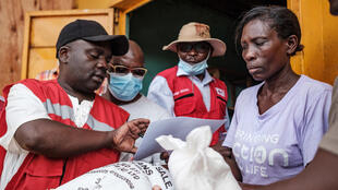 Red Cross volunteers register people during the first day of the government's food distribution for people who have been affected by the lockdown in Kampala, 4 April 2020.