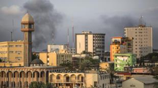 De la fumée noire s'échappe dans le ciel de Libreville, alors que le soleil se couche sur la capitale.