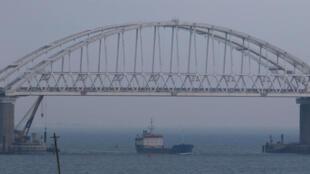 Un navire passe sous le pont reliant le reste de la Russie à la Crimée dans le détroit de Kertch. Ce détroit relie la mer noire à la mer d'Azov.