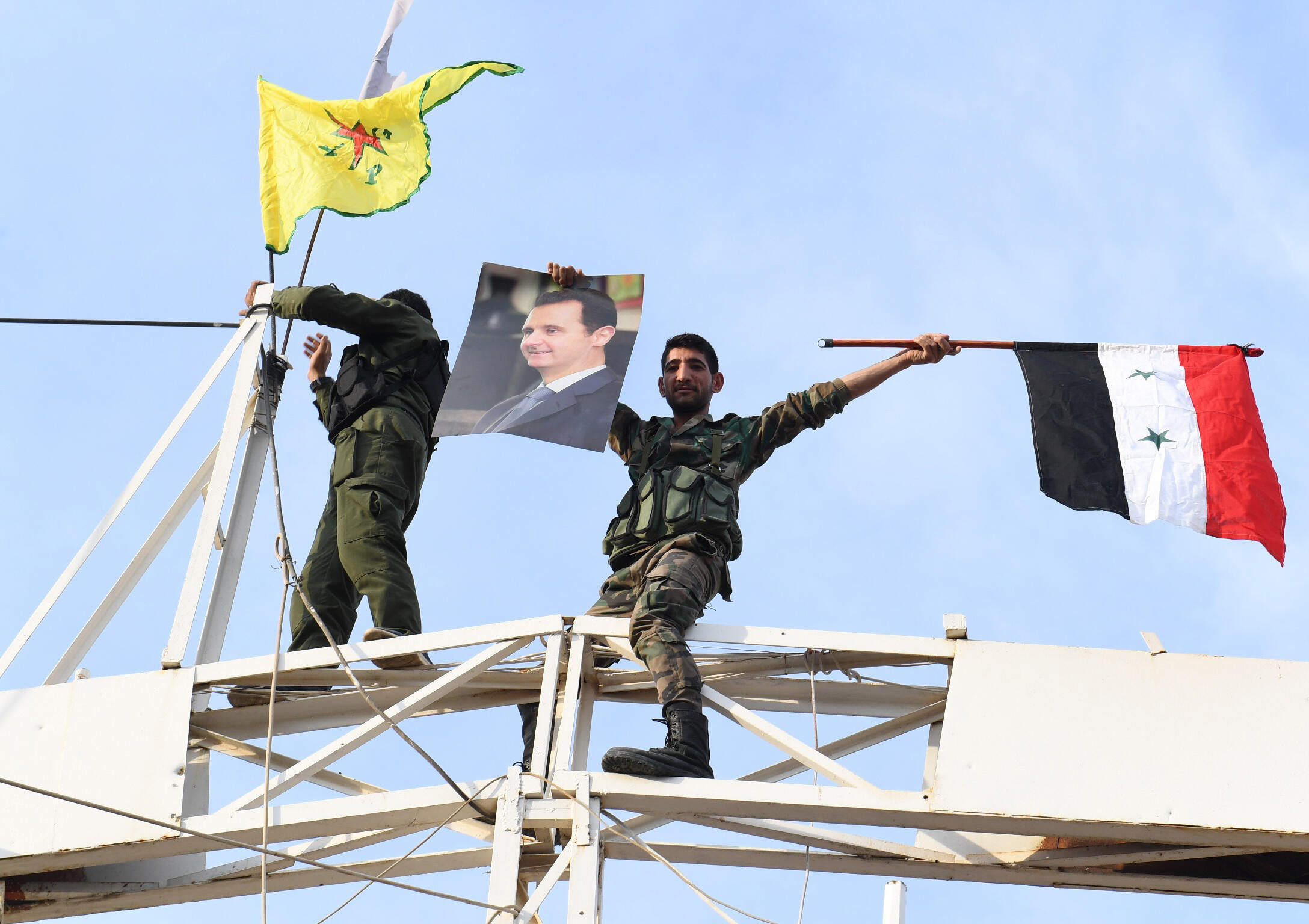 Un soldat syrien arbore un portrait du président Bachar el-Assad ainsi que le drapeau syrien et celui des YPG, le 18 octobre 2019 à Kobané.