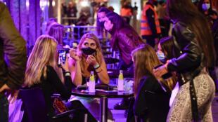 Varias mujeres toman algo en la terraza de un bar durante el ensayo clínico para una posible reapertura de los locales nocturnos, el 20 de mayo de 2021 en la localidad catalana de Sitges, al noreste de España