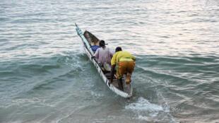 Des pêcheurs ivoiriens se lancent dans l'océan Atlantique pour entamer leur journée, à Grand Béréby, dans le sud-ouest de la Côte d'Ivoire, en février 2014.
