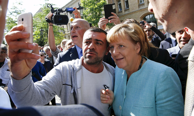 Канцлер Германии Ангела Меркель фотографируется с мигрантом около Федеральной службы миграции в Берлине, 10 сентября 2015.