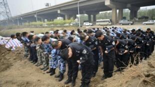 Miembros del ejército rinden homenaje a las víctimas de las explosiones de Tianjin durante una ceremonia, 18 de agosto de 2015.