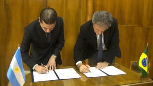 Os ministros Francisco Cabrera (à esquerda) e Marcos Pereira assinam acordo em Buenos Aires.