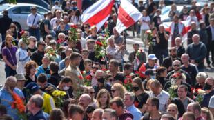 Los partidarios de la oposición de Bielorrusia se reúnen cerca de una estación de metro en el centro de Minsk el 15 de agosto de 2020 para asistir a la ceremonia fúnebre de un manifestante