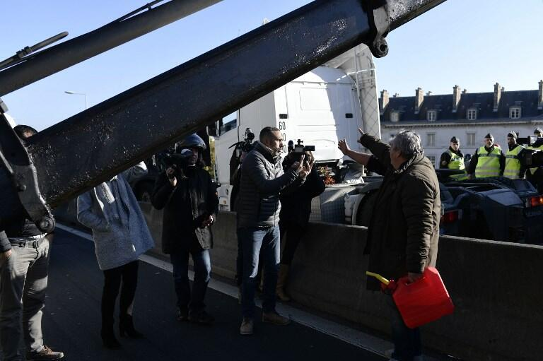 A motorist argue with a stallholder taking part in a go-slow operation on a motorway near Paris on 6 November