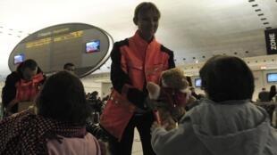 Un empleado del aeropuerto Charles de Gaulle reparte juguetes entre los niños que han pasado la noche allí.