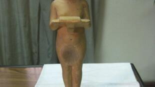 A limestone statue of Pharaoh Akhenaten holding an offering table