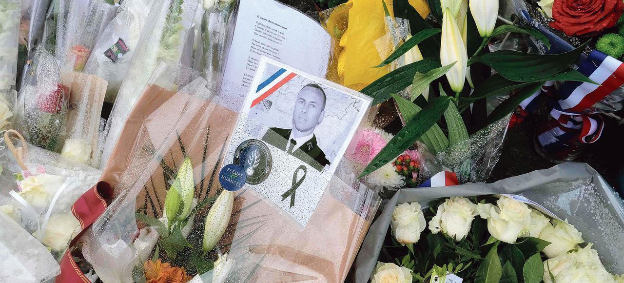 Des bouquets de fleurs déposés, le dimanche 25 mars 2018, devant la gendarmerie de Carcassonne, avec un portrait du lieutenant-colonel Beltrame.