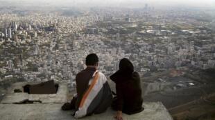 Un couple assis devant un panorama de la ville de Téhéran.