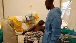 Medical stuff and an Ebola survivor treat Ebola patient Ibrahim Mupalalo inside the Biosecure Emergency Care Unit (CUBE) at the ALIMA (The Alliance for International Medical Action) Ebola treatment centre in Beni, in the Democratic Republic of Congo