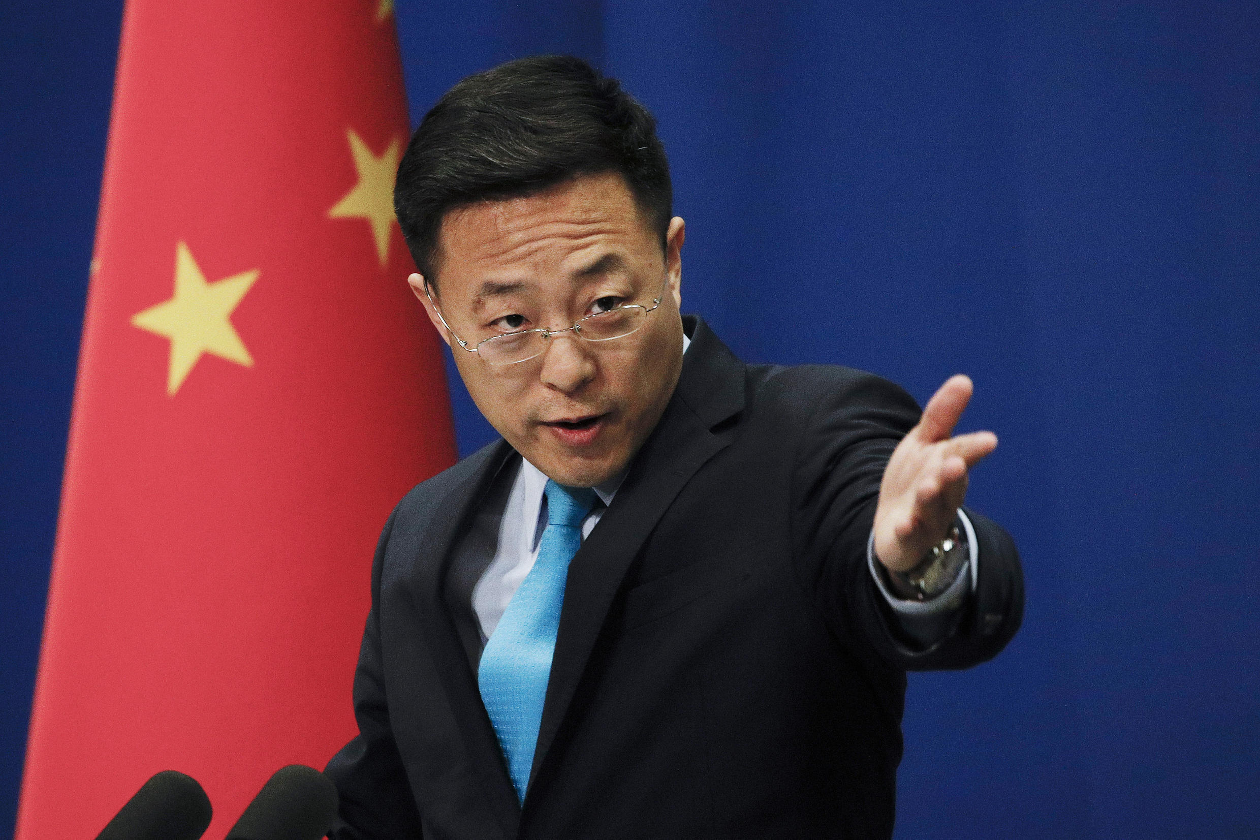 In this file photo taken Monday, Feb. 24, 2020, Chinese Foreign Ministry new spokesman Zhao Lijian gestures as he speaks during a daily briefing at the Ministry of Foreign Affairs office in Beijing.