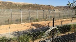la ligne de démarcation à Majdal al-Shams, principale ville du Golan contrôlée par Israël où  les combats  font  rage derrière la colline.