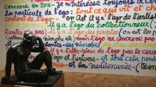 Escultura de Aristide Maillol diante de uma parede com interferências verbais coloridas de Ben