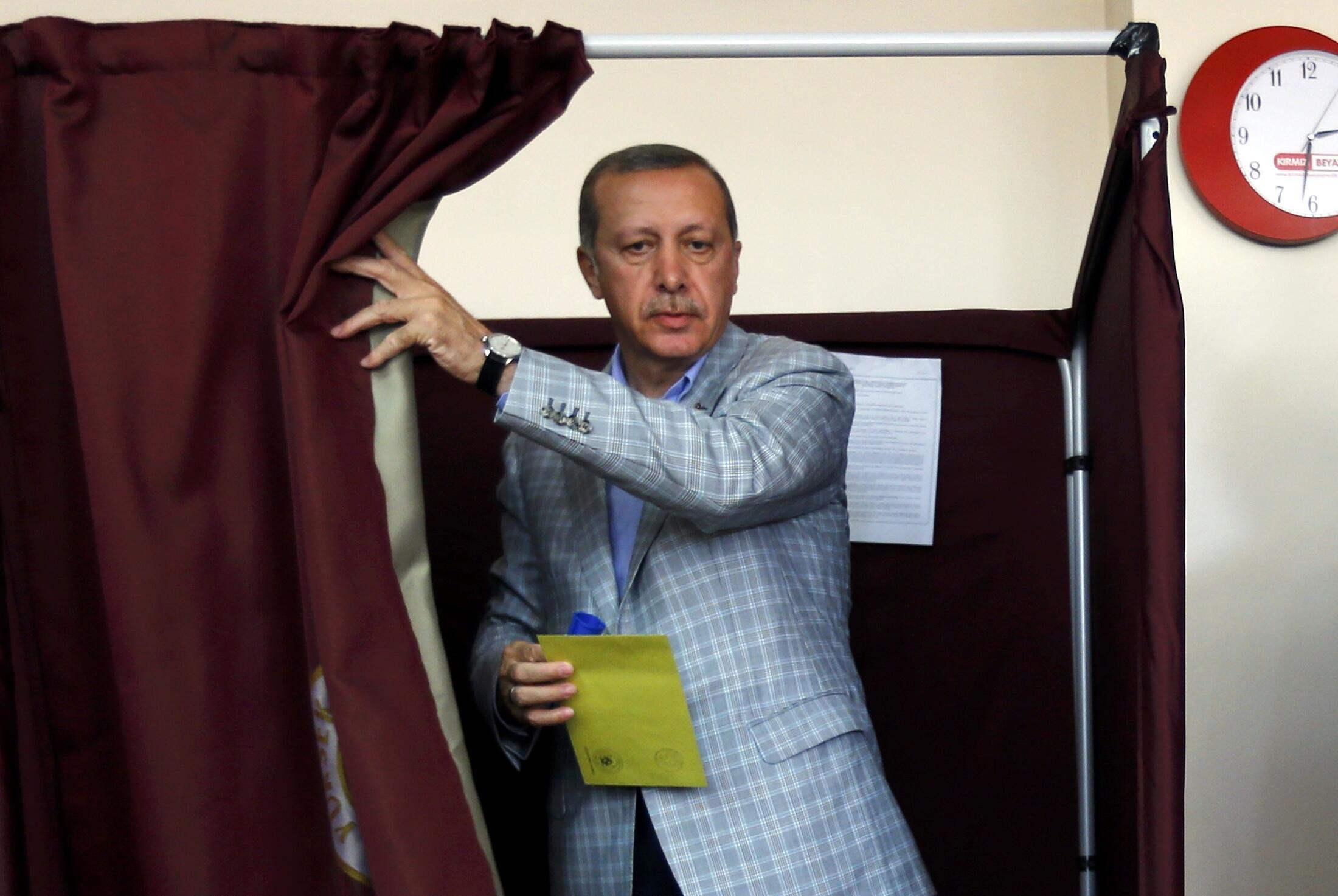 O primeiro ministro turco, Recep Tayyip  Erdogan, em cabine eleitoral no primeiro turno da eleição presidencial.