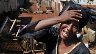 A Guinean weeps after her relatives were killed by troops in Ratoma
