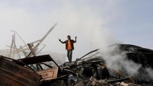 Un homme se tient sur les débris d'un bâtiment bombardé par la coalition arabe menée par Riyad, à Sanaa, le 2 juillet 2020.