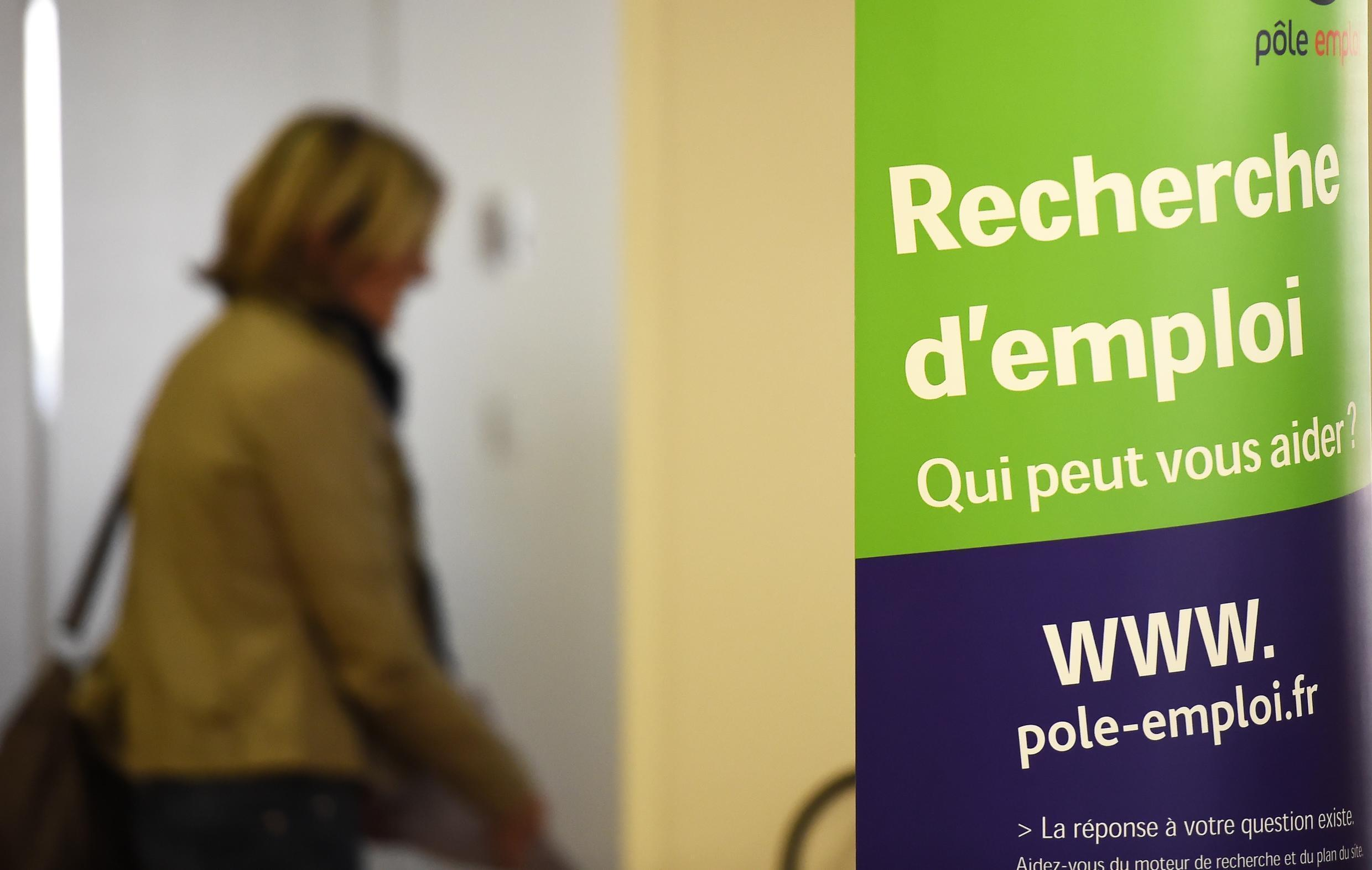 """A woman walks next to a boards that reads """"Looking for a job, who can help you?"""" in a branch of France's national employment agency Pole Emploi next in Montpellie, southern France"""