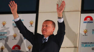Turkish President Tayyip Erdogan greets supporters gathered in front of the AKP headquarters in Ankara