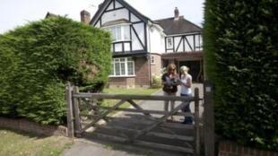 Policiais britânicas deixam a casa da família al-Hilli em Claygate, subúrbio de Londres.