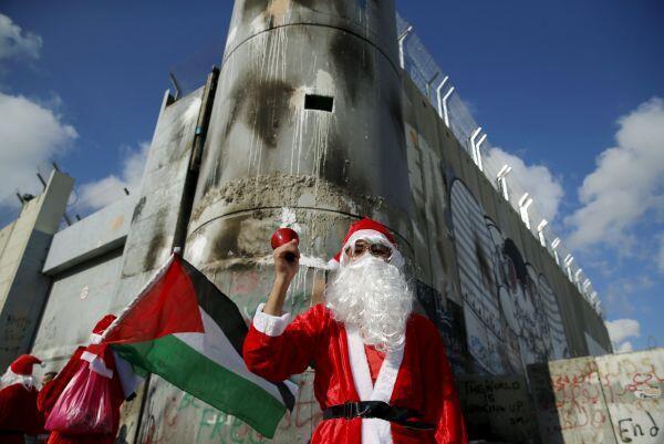 Un manifestante palestino disfrazado de Papá Noel/Santa Claus frente a la barrera de seguridad israelí en Belén, el 18 de diciembre de 2015.