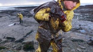 Un militar con una bolsa llena de petróleo, el 28 de diciembre de 1999 en Bretaña, Francia.