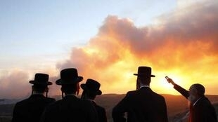 Ultra-Orthodox Jewish men look at a forest fire that broke out near kibbutz Beit Oren in the north of Israel