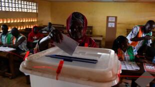 Une femme dépose son bulletin de vote dans l'urne le 13 octobre 2018 à Bouaké, en Côte d'Ivoire.