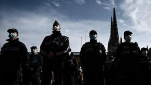 Policías con mascarilla observan un minuto de silencio ante el Ayuntamiento de Burdeos en memoria del profesor asesinado tras mostrar unas caricaturas de Mahoma en clase, el 19 de octubre de 2020 en esa ciudad francesa